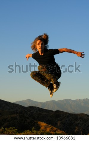 Young male in casual attire jumping above mountain peaks, facing forward, arms widespread, knees up.