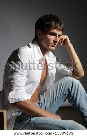young male in white shirt on grey baclground - stock photo