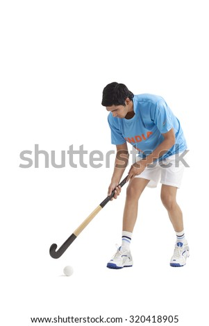 Young male Indian player practicing hockey isolated over white background - stock photo