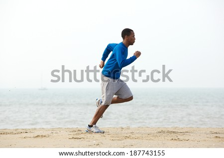 Young male jogger exercising at the beach in sportswear  - stock photo
