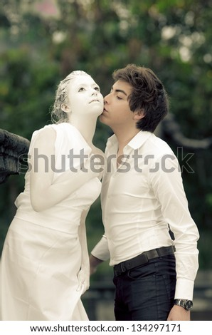 Young male KISSING at a young female MODEL DRESSED AS A carved statue - stock photo