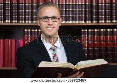 Young male lawyer reading legal book at courtroom - stock photo