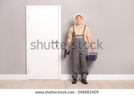 Young male locksmith holding a drill and a toolbox and standing next to a door indoors - stock photo