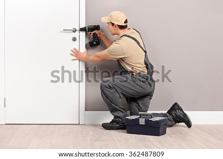 Young male locksmith installing a lock on a new white door with a hand drill - stock photo