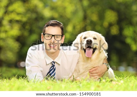 Young male lying on a green grass and hugging his labrador retriever dog in a park - stock photo