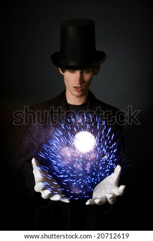 Young male magician performing a magic trick - stock photo