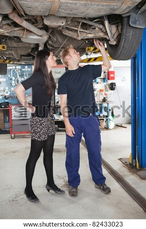 Young male mechanic and woman looking at underboy of car in auto repair shop - stock photo