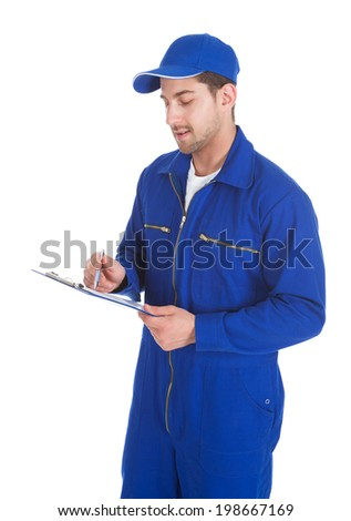 Young male mechanic in overall writing on clipboard over white background - stock photo