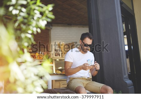 Young male millionaire in stylish sunglasses chatting on his smart phone while sitting near own new healthy cafe with natural food, man host of small bakery reading text message during work break - stock photo
