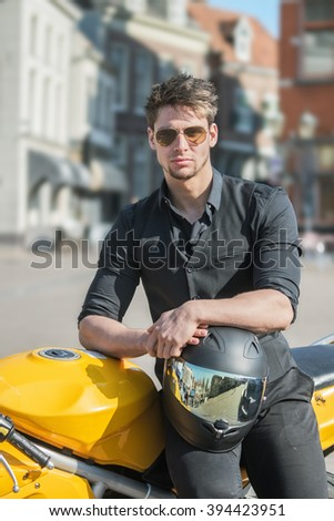 Young male model on motorcycle outdoors on a sunny day - Attractive young man - stock photo