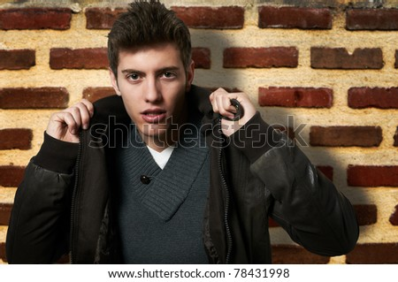 Young male model posing at brick wall - stock photo
