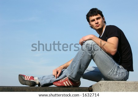 Young male model sitting on the stone blocks - stock photo