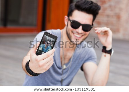 young male model smiling and making self portrait with a smart-phone - stock photo