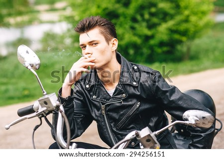 Young Male Model with retro hairstyle on a motorcycle - stock photo