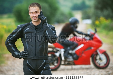 Young male motorcyclist was talking on his cell phone. - stock photo