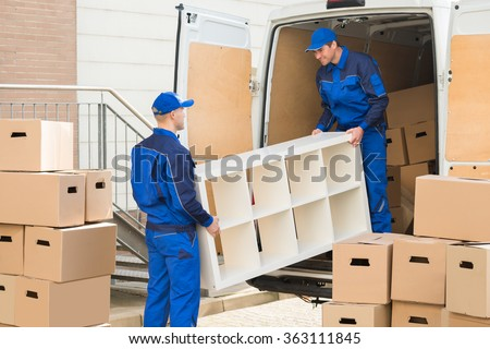 Young male movers unloading furniture and cardboard boxes from truck on street - stock photo