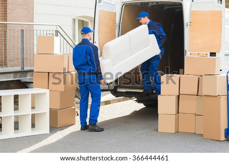 Young male movers unloading sofa from truck on street