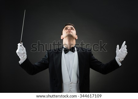 Young male music conductor looking up while holding baton against gray background