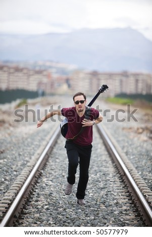 Young male musician running on railway road. - stock photo