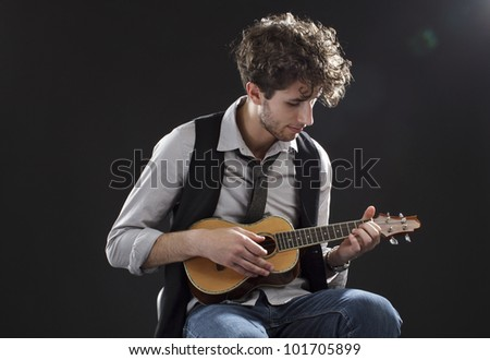 Young male musician sits and plays a ukulele. Backlighting, dark background, copy space, horizontal. - stock photo