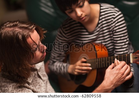 Young Male Musician Teaches Female Student How To Play the Guitar. - stock photo