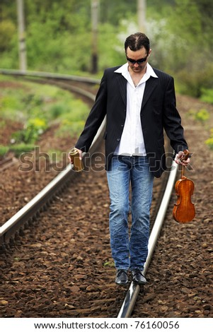 Young male musician walking on the railway - stock photo