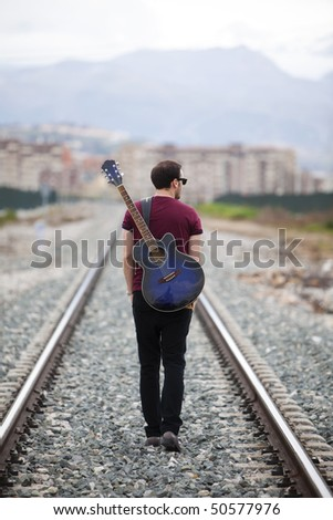 Young male musician walking with his acoustic guitar. - stock photo