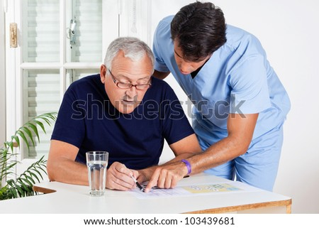 Young male nurse helping senior man in solving puzzle