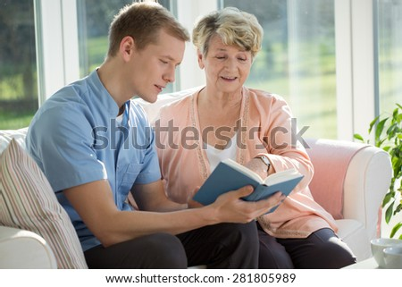 Young male nurse reading to his elderly patient - stock photo