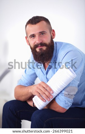 Young male office worker sitting on chair in office . - stock photo