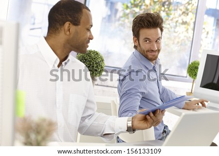 Young male office workers sitting at desk, one passing folder to the other in bright office. - stock photo
