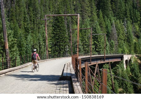 young male on a  bicycle riding on dirt roads through the mountains of Northern Idaho
