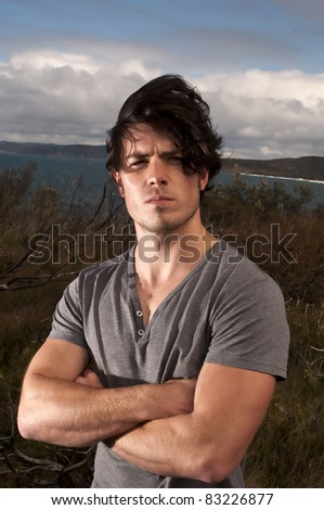 Young male on a windy cliff top - stock photo