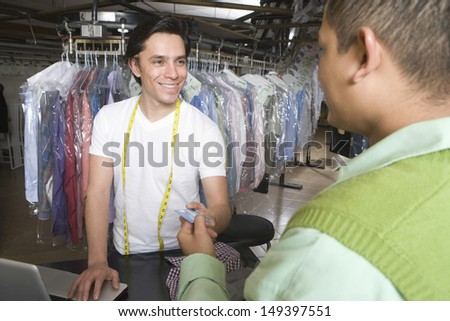 Young male owner receiving credit card from customer at counter in laundry