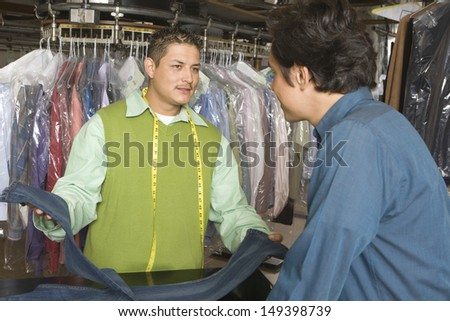 Young male owner showing dry cleaned jeans to customer at counter in laundry