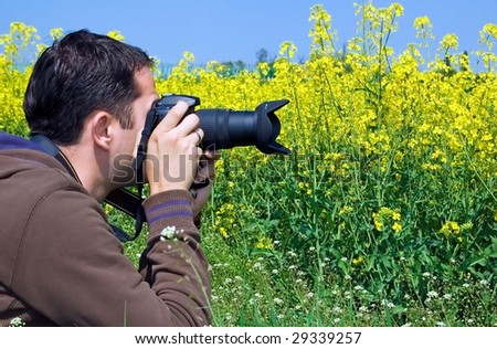 Young male photographer taking photos of yellow flower field - stock photo