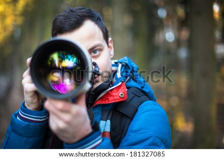 Young, male photographer taking photos with his huge, new, shiny, fast prime professional telephoto lens - stock photo