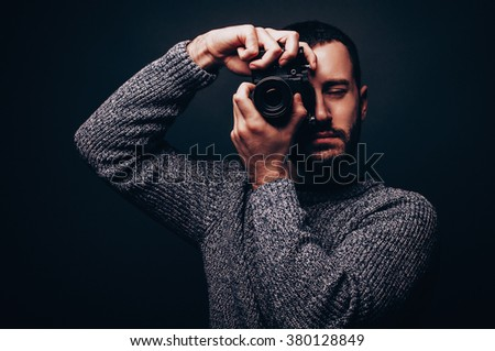 Young male photographer with beard taking pictures facing camera lens to you