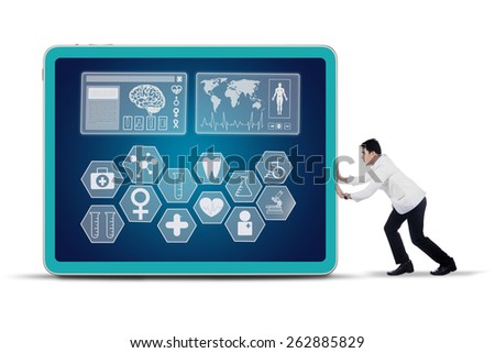 Young male physician pushing medical symbol on a virtual screen, isolated on white background - stock photo