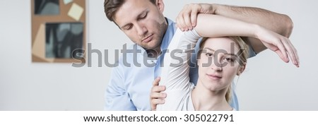 Young male physiotherapist is rehabilitating female patient - stock photo
