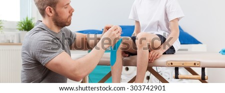 Young male physiotherapist working with little patient - stock photo