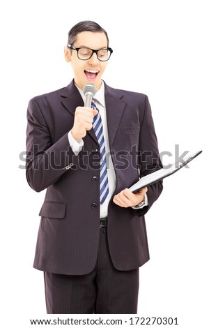 Young male presenter holding microphone and clipboard, isolated on white background - stock photo