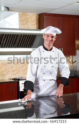 young male professional chef cleaning in commercial kitchen