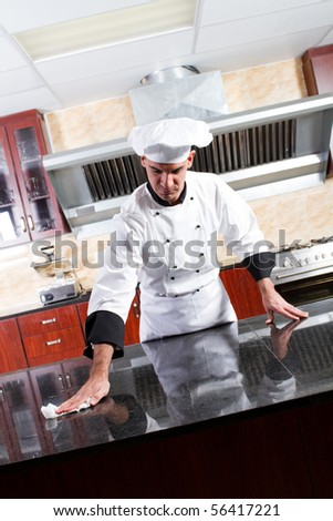 young male professional chef cleaning in commercial kitchen - stock photo