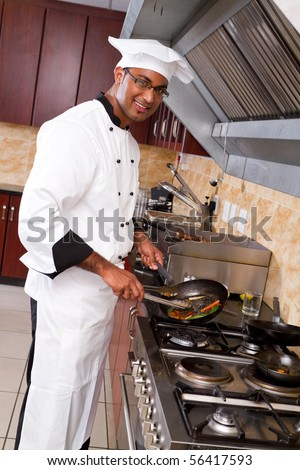 young male professional chef cooking in commercial kitchen - stock photo