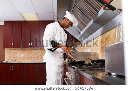 young male professional chef cooking in commercial kitchen