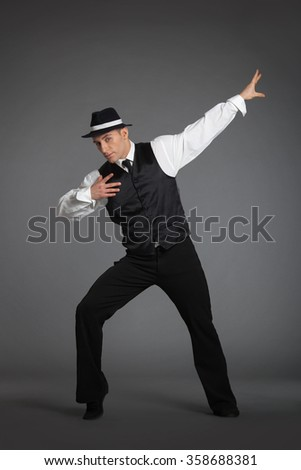Young male professional dancer dancing in studio isolated on gray background. - stock photo