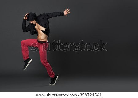 Young male professional dancer dancing in studio isolated on gray backhround. - stock photo