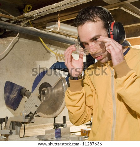 Young male putting on his safety goggles before using his power tools - stock photo