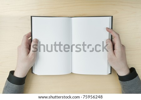 Young male reading an empty open book on a desk - insert your own message - stock photo